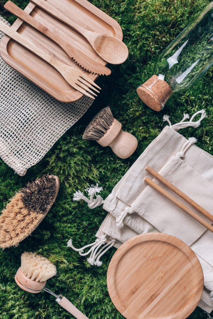 Various sustainable zero waste kitchenware utensils and dishware: cotton bag, bamboo cutlery, glass